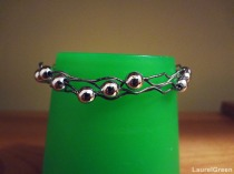a photo of a wire bracelet with metal beads on it